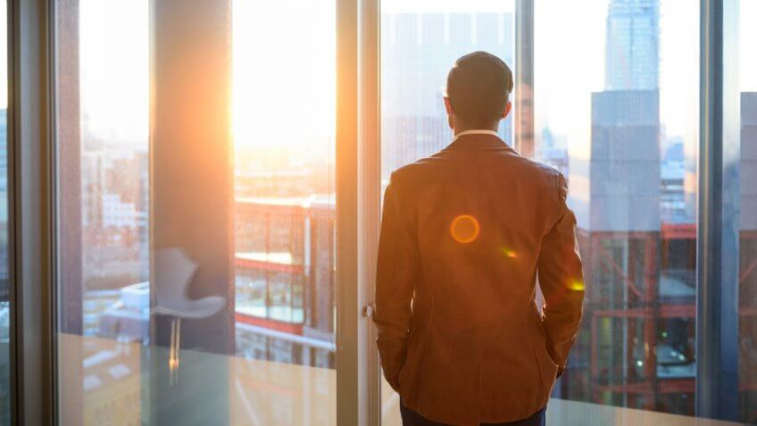 Male office worker looking at view through window of modern office over city.