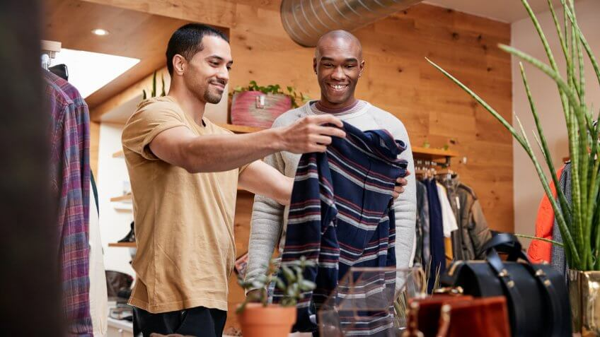 Two young men holding up clothes to look at in clothes shop.