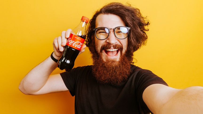 Cheerful smiling bearded hipster man with Coca Cola Drink in hands. Man holding Coca Cola