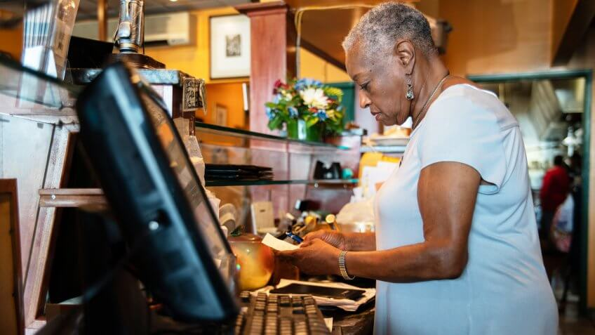 The senior Black woman working with the computerized cash register behind the counter in the small restaurant in New York State, USA.