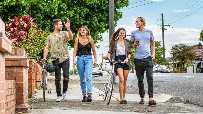 Four Australian friends walking in the street of Sydney on a sunny day.
