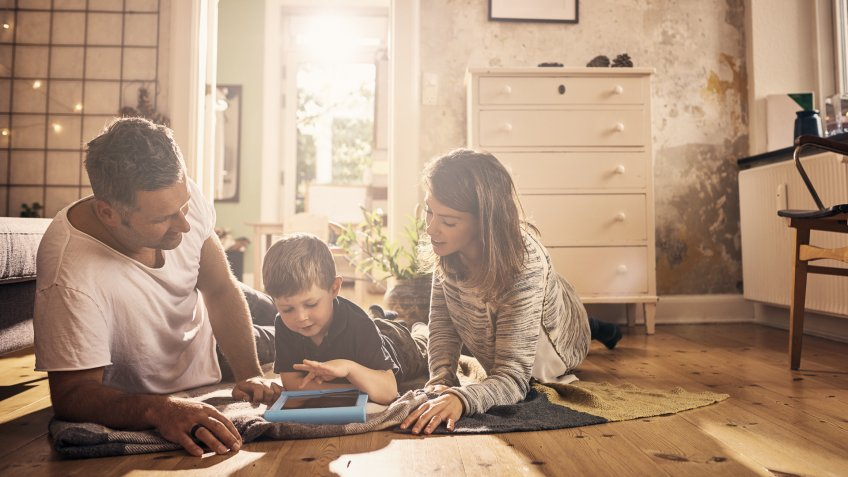 Shot of a little boy and his parents using a digital tablet together at home.