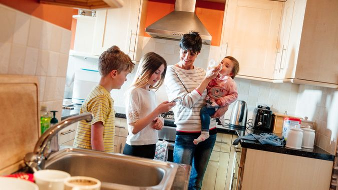 Multitasking mum is tending to all of her children at once in the kitchen of their home.