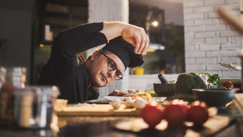 Photo of an experienced chef adding spices to the meal he is preparing.