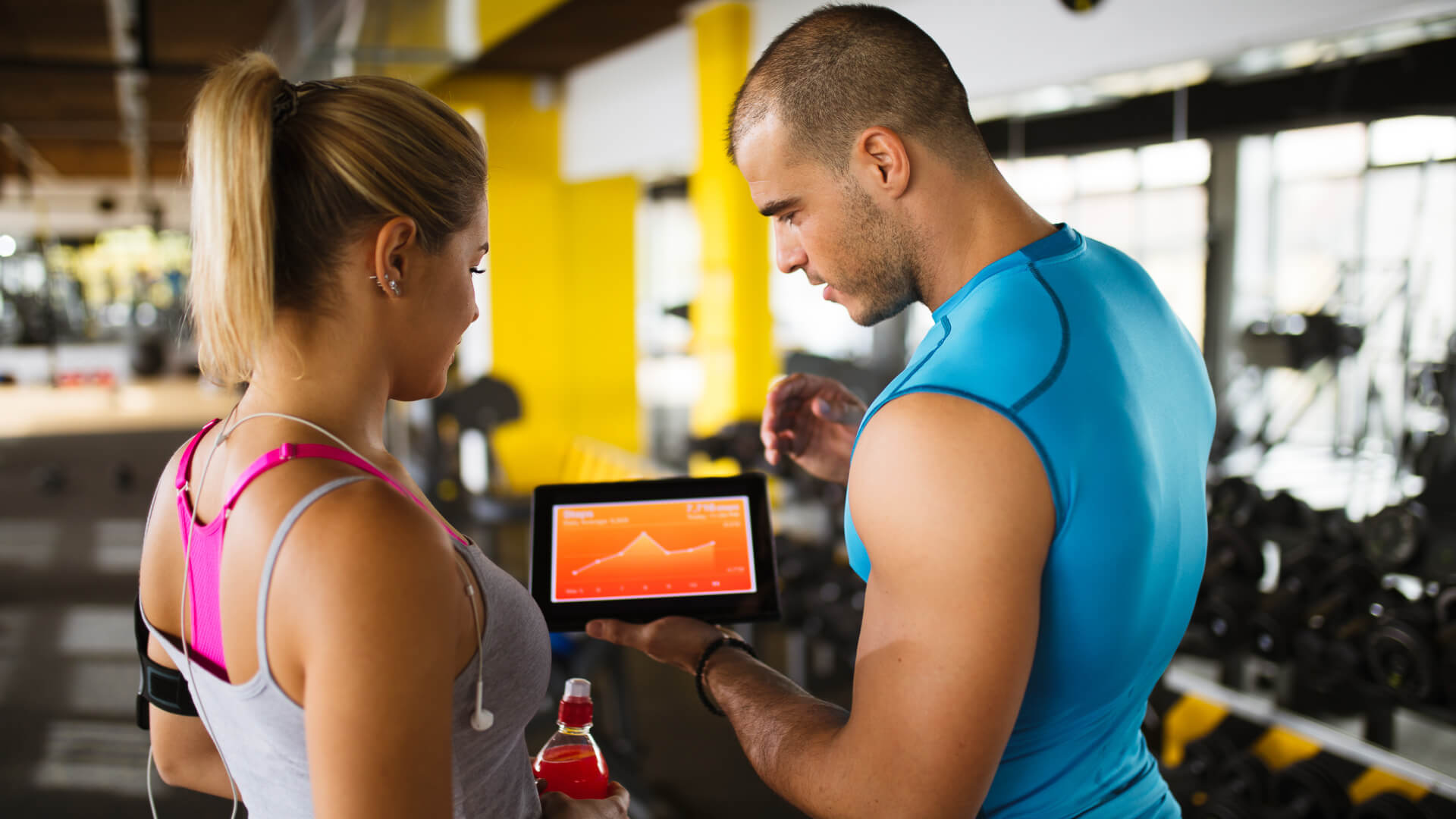 Young sporty woman is discussing workout plan, progress and statistics with her fitness instructor using digital tablet.