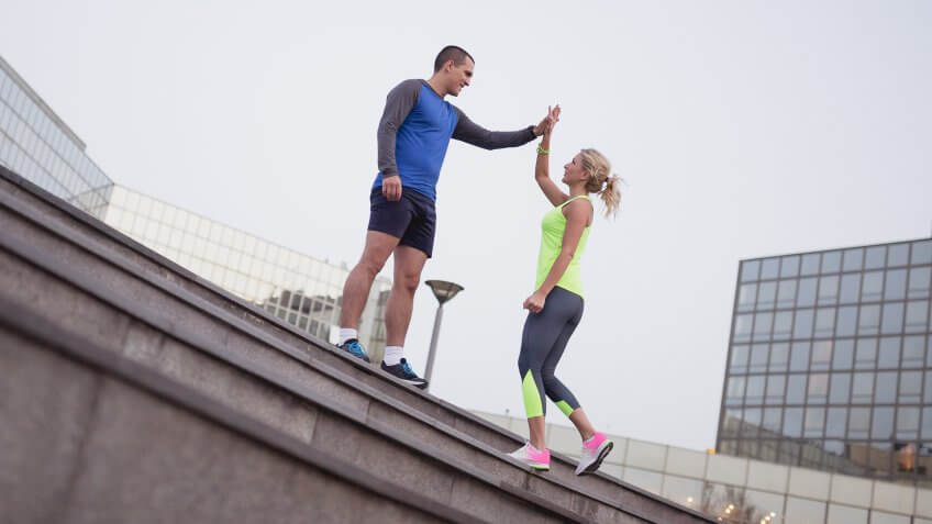 Young couple, athletes, training outdoors in the urban environment.