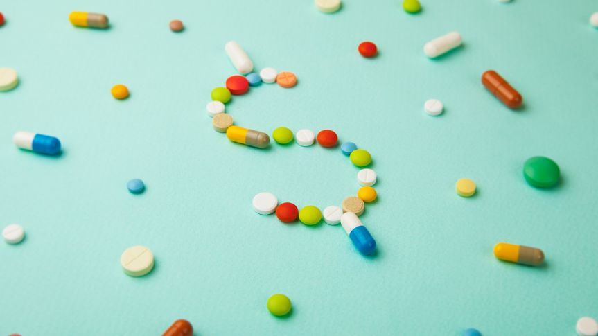 Symbol of money dollar from colored pills and capsules on  green background.