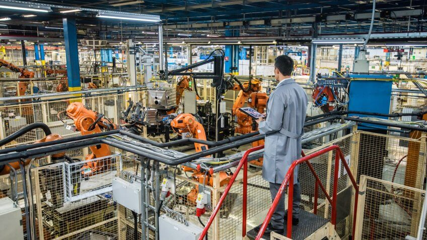 Male factory engineer inspecting the work process of the robots performing their operations in appliance manufacturing factory.