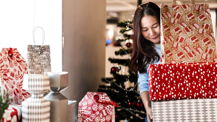 Asian woman carrying stacked of christmas gift boxes, she prepare and decorate her home for Christmas festival and night party.