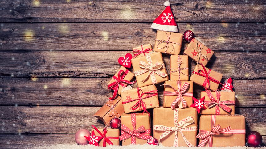 Christmas background with decorations and gift boxes on wooden board.