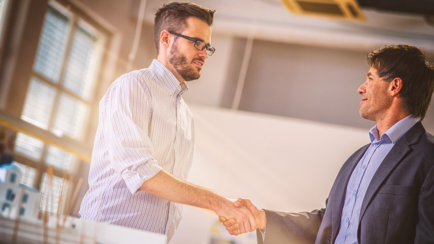 Architect shaking hands with his client while standing beside a desk with an architectural model.