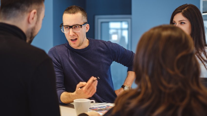 Man with glasses aggressively talking at the office meeting to his colleagues.