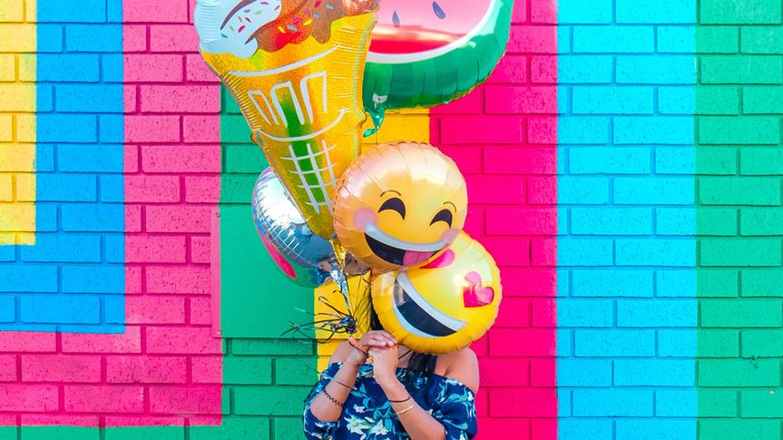 woman holding colorful balloons.