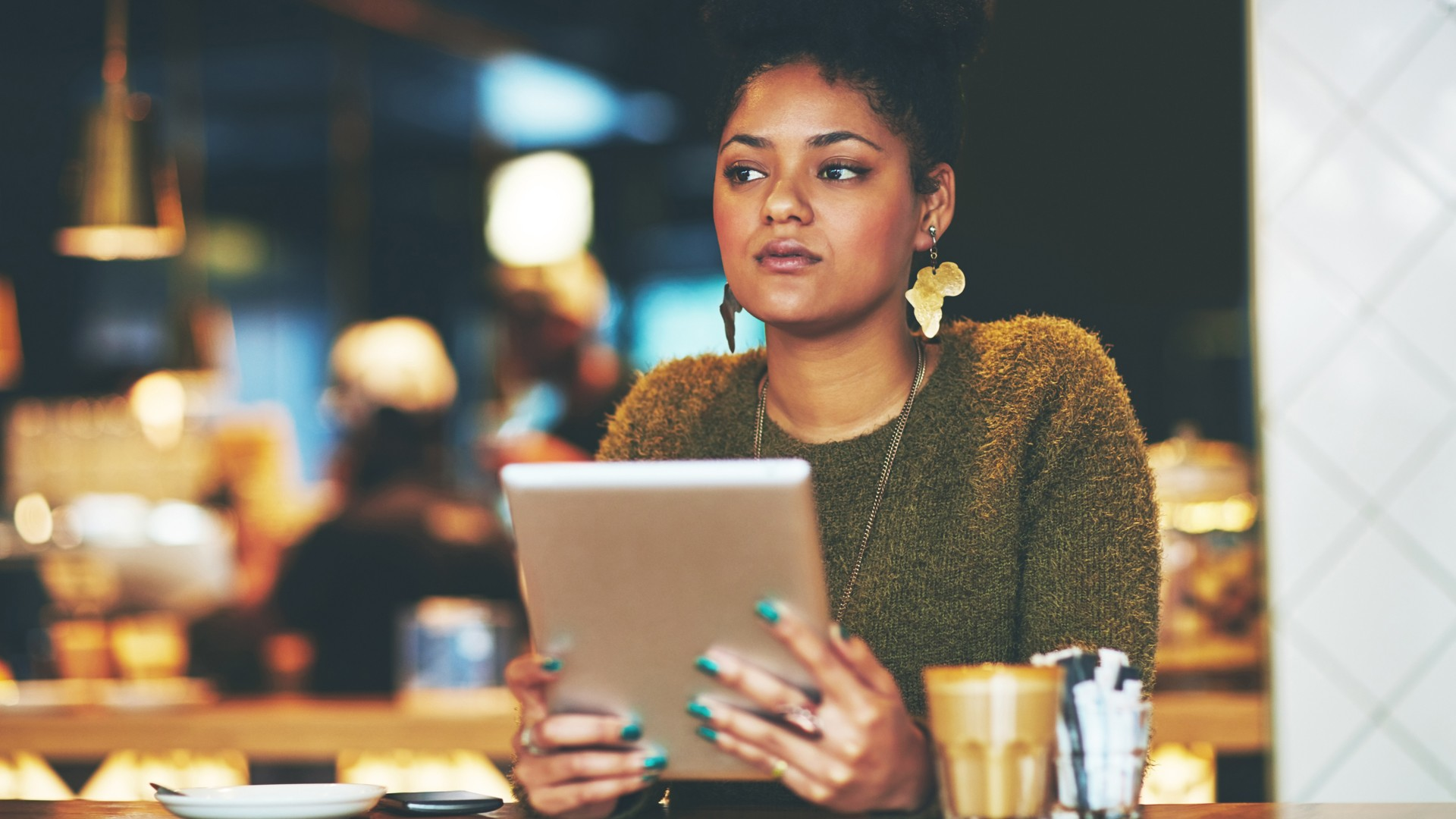 Shot of an attractive young woman looking thoughtful while using a digital tablet in a cafe.