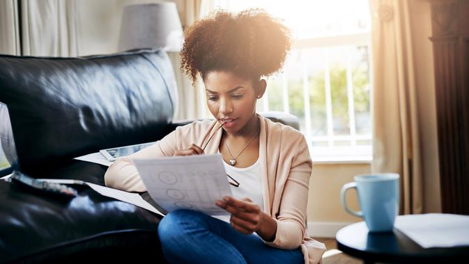Shot of a young woman going through her paperwork at home.