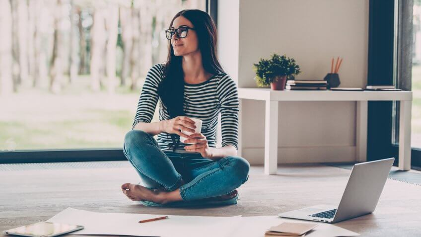 woman sitting on floor surrounded by papers and laptop
