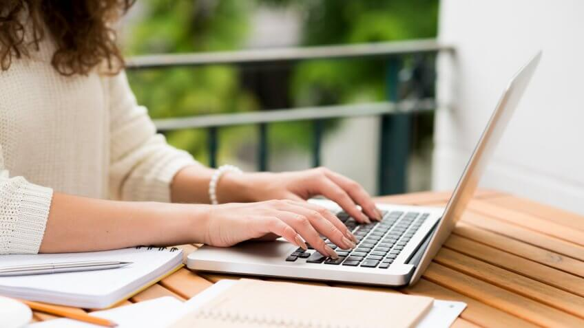 Side view of woman working on laptop, selective focus.