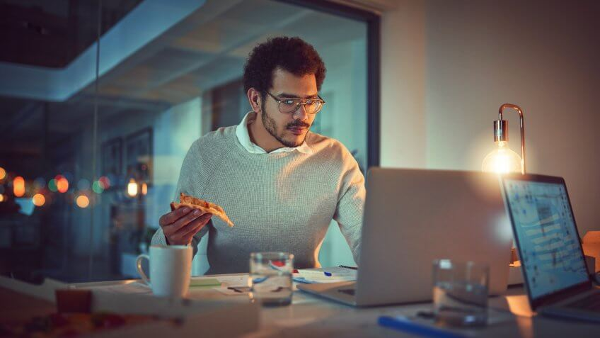 Shot of a young designer eating pizza while working late in an office.