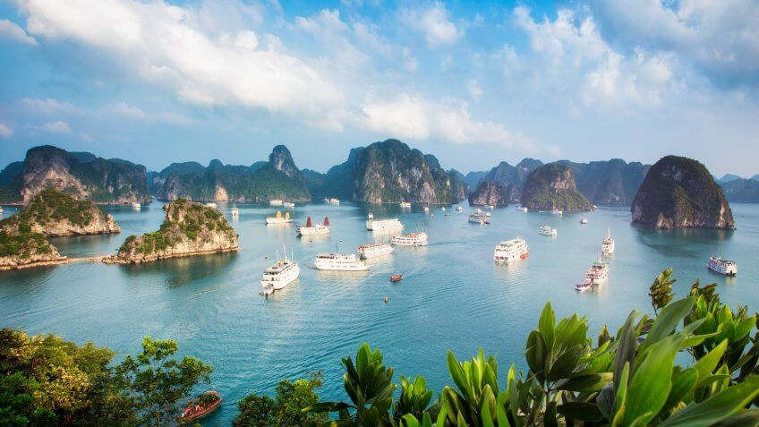Halong Bay Vietnam panorama at sunset with anchored tourist ships photographed from the top of a cliff.