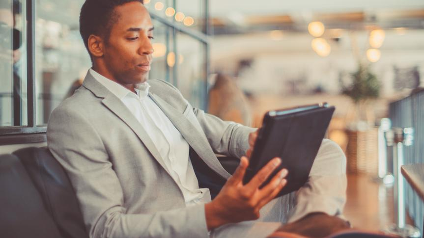 Young businessman using digital tablet in hotel lobby.