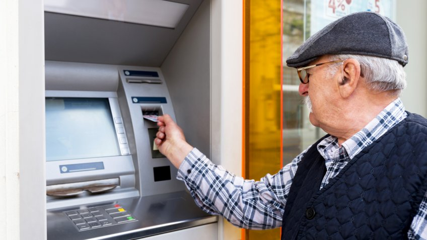 elderly man inserting credit card to ATM outdoor.