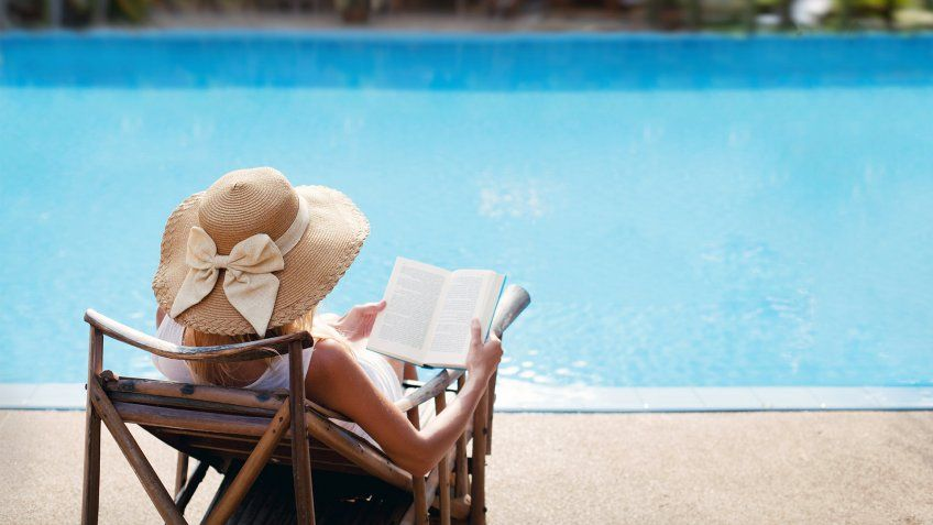 traveler enjoying a book by the pool on vacation