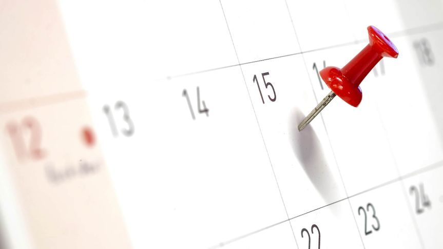 Embroidered red pins on a calendar on the 15th with selective focus.