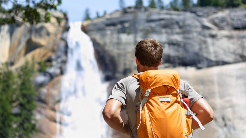 hiking with a backpack up to a waterfall
