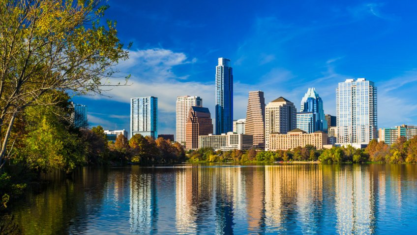 Downtown Austin skyline during Autumn with beautiful lake reflections and a deep blue sky with cloud.