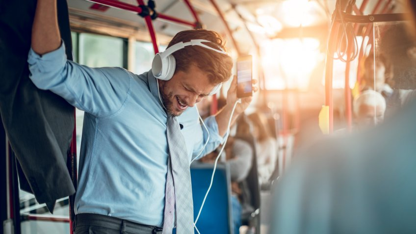 Close up of a businessman listening to music while riding in a bus.