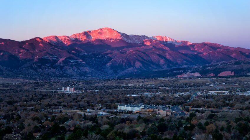 The summit of Pikes Peak glows in the morning sunrise as the streets and business office are below the mountain.