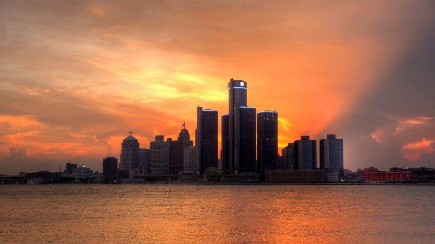 Detroit city skyline along the Detroit River at sunset.