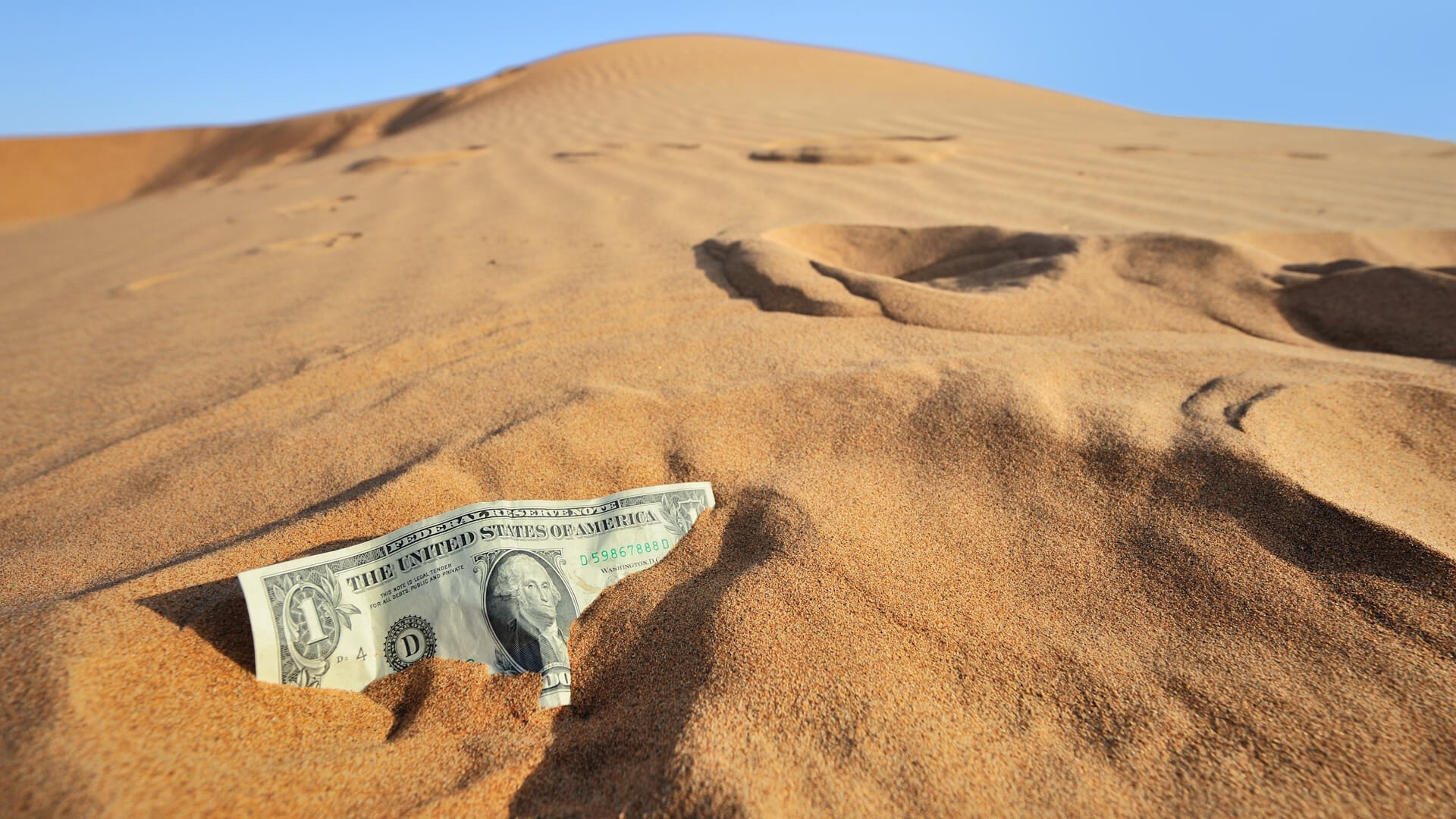 close up of dollar bill stuck in sloping sand, concept image of financial crisis and related currency turmoils.