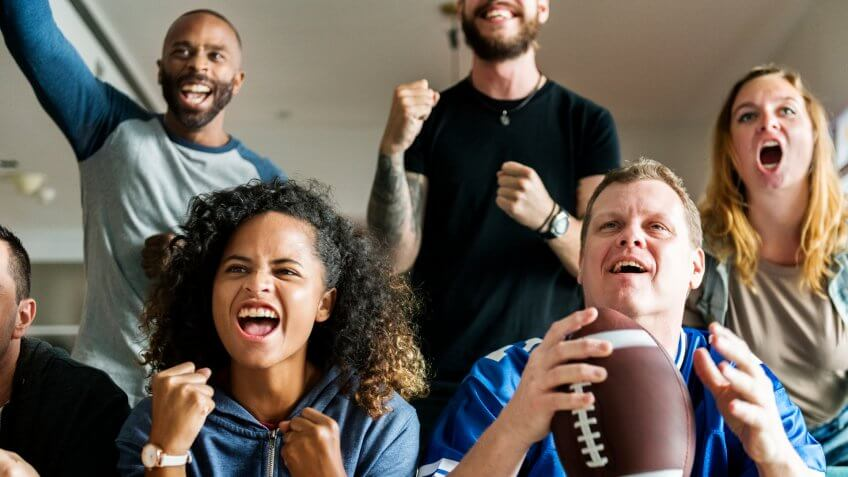 Friends cheering American football together