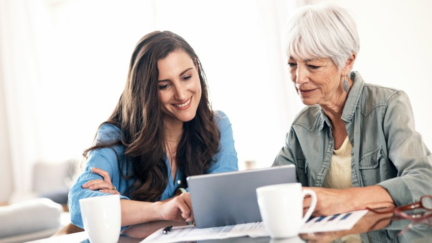 Shot of a young woman using a digital tablet with her elderly mother to help work on her home finances.