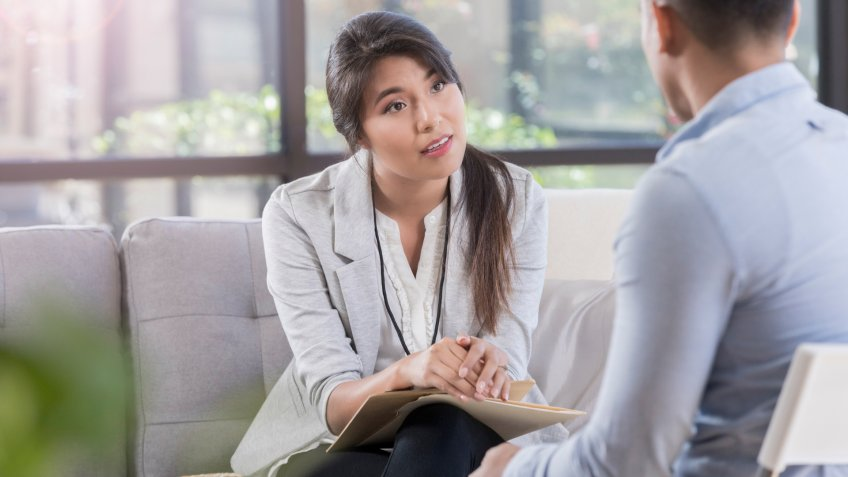 While sitting in a comfortable waiting room, female doctor listens to her patient about mental health problems.