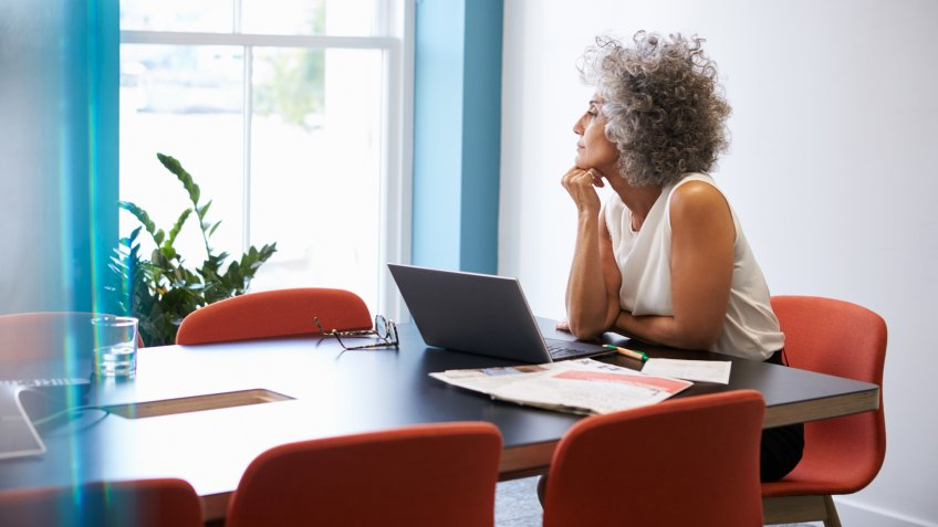 Middle aged woman looking out of the window in the boardroom.
