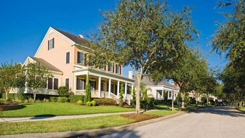 Picturesque luxury home with wooden verandah in traditional style overlooking quiet suburban streets under clear blue panoramic skies in this tranquil Florida community.