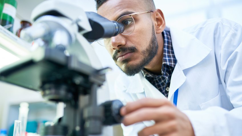 Portrait of young Middle-Eastern scientist looking in microscope while working on medical research in science laboratory, copy space.