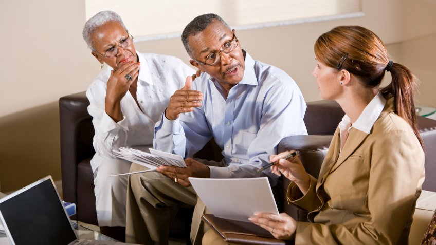 Senior African American couple meeting with financial adviser discussing documents.