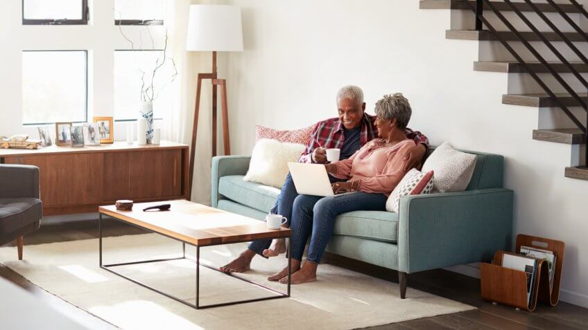 Senior Couple Sitting On Sofa At Home Using Laptop To Shop Online.