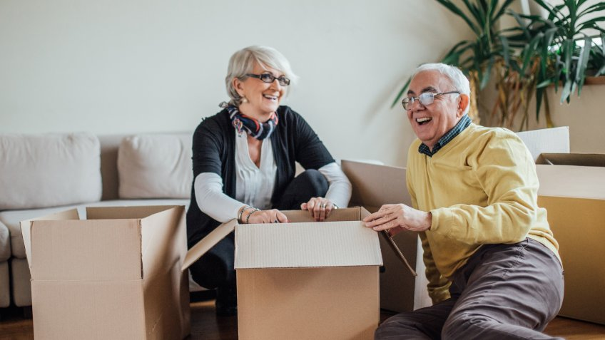 Mature couple smiling and unpacking paper containers at new apartment.