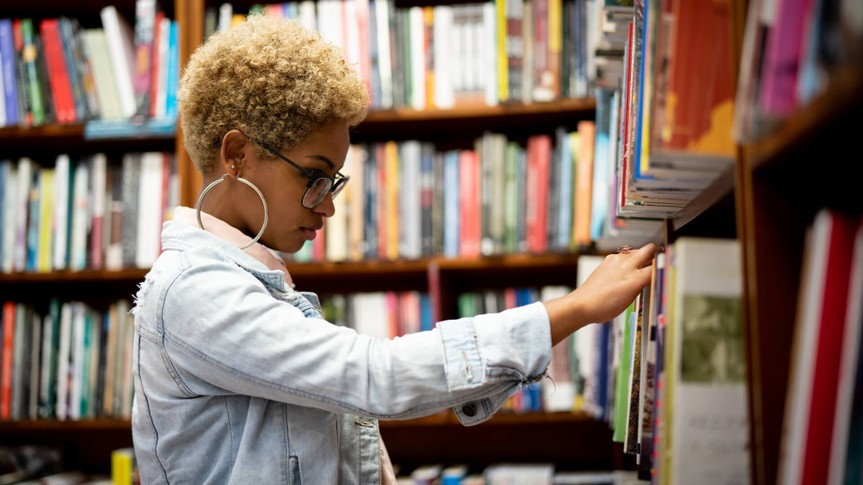 student browsing books in a library bookstore