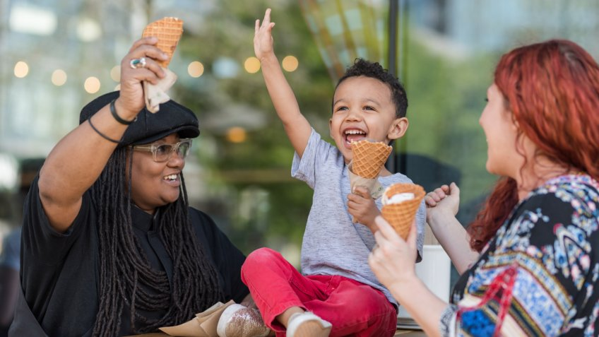 Two moms eat ice cream with their three-year old son