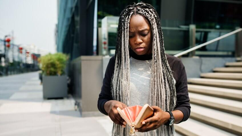 Woman checking her wallet with a concerned expression