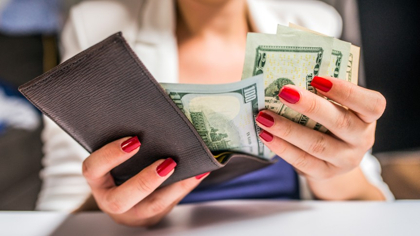 people, business, finances and money concept - close up of businesswoman hands holding open wallet with dollar cash.