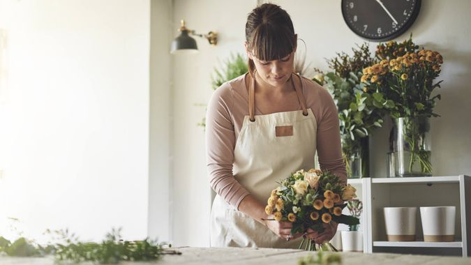 Young female florist putting together a bouquet of mixed flowers while working at a table in her flower shop.