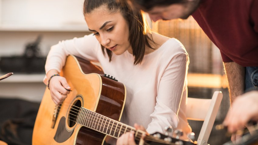Young man teaching a teenage girl to play the guitar.