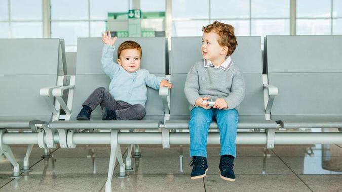 Children waiting near airport boarding gate.