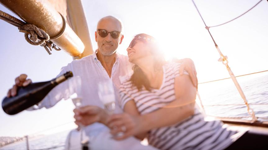 Loving mature couple enjoying a romantic sunset cruise on a yacht at sunset with champagne to celebrate a special occasion on holiday.